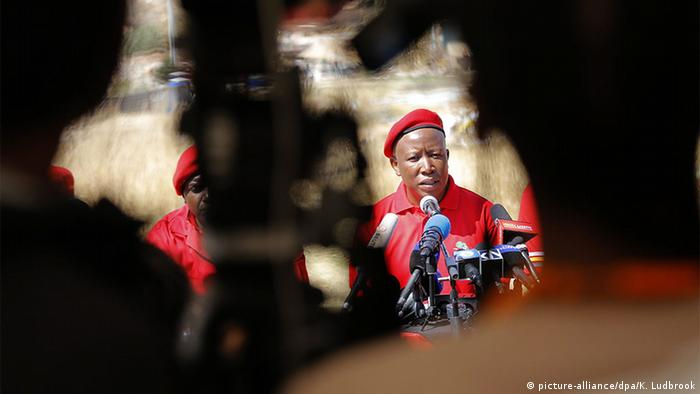 EFF leader Julius Malema in a red outfit in front of TV cameras.