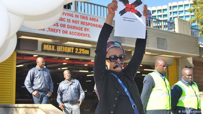 A woman holds up a poster reading #SABCCensorship #Notinmyname