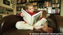 Deutschland Bonn Lesender Junge vor Bücherwand