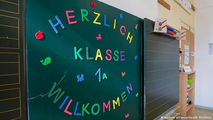 Colorful letters on a school chalkboard read 'Welcome Class 1A!' in German
