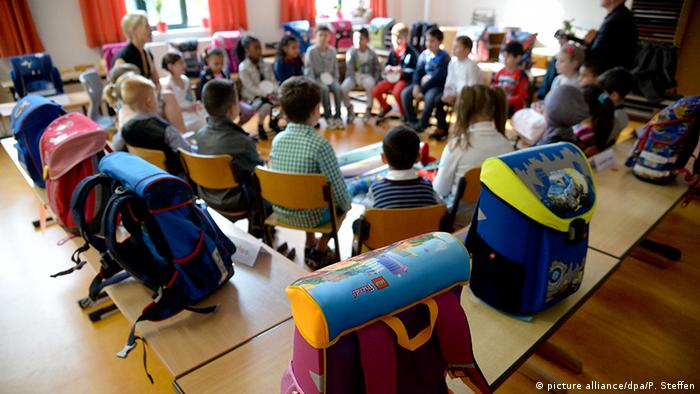 A group of elementary students sit in a circle in a classroom