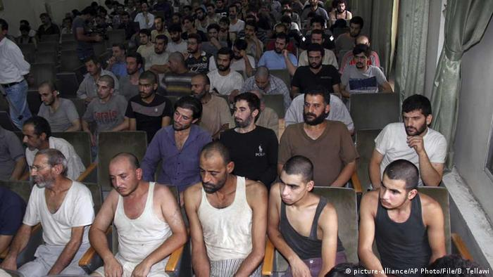 A group of men sit in rows in a courtroom, wearing singlets, after being released form jail in Syria.