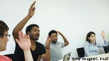mehrere junge Männer und ein Frau melden sich im Unterricht