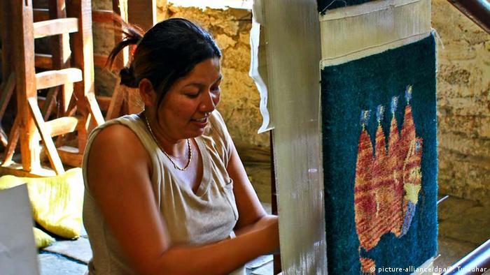Eine tibetische Frau webt in einem Flüchtlingslager einen Teppich um ihren Lebensunterhalt zu verdienen. (Foto: picture-alliance/dpa/P. Tuladhar)
