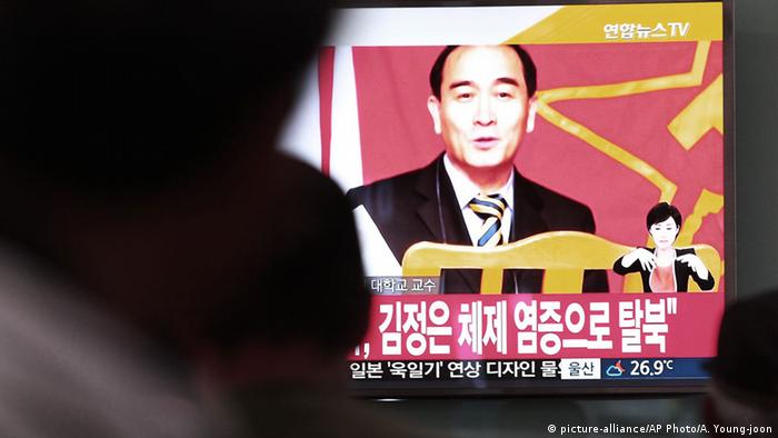 People watch the news on a giant screened TV in Seoul, showing a file image of Thae Yong Ho.