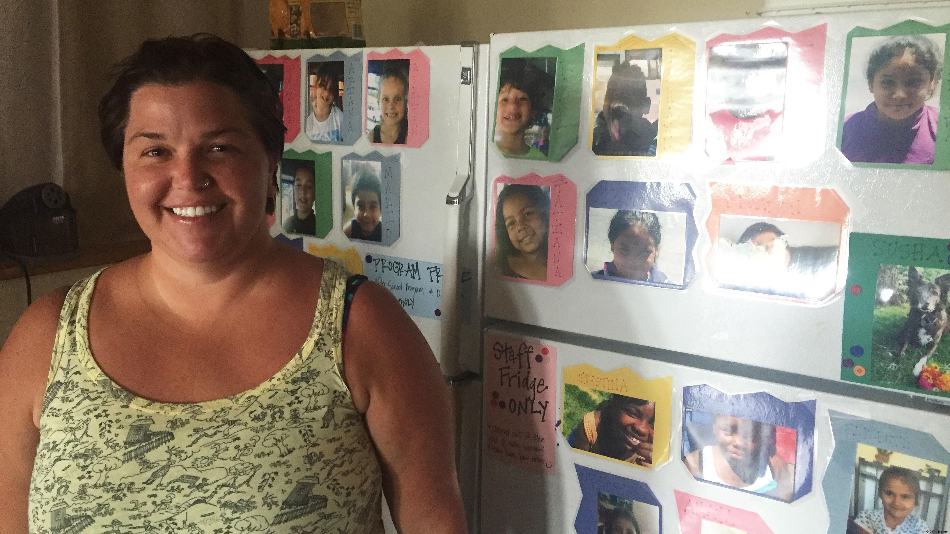 Megan Vizina stands in front of photos of the kids she works with