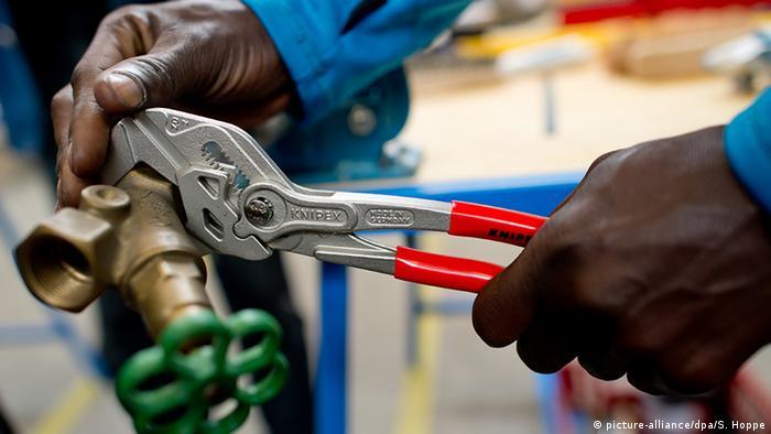 Die Hände eines Handwerkers mit schwarzer Haut sind zu sehen, der eine Zange an einen Wasseranschluss setzt