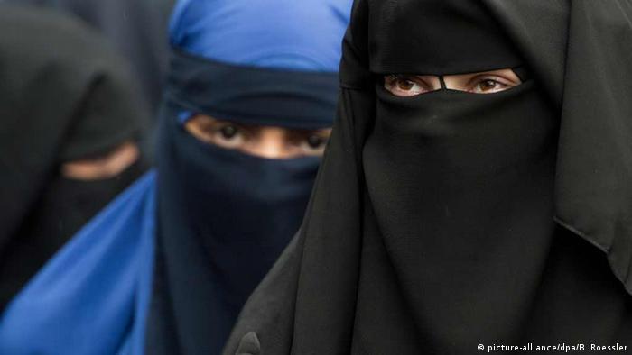 Три женщины-мусульманки в черной и синей одежде, скрывающей лицо