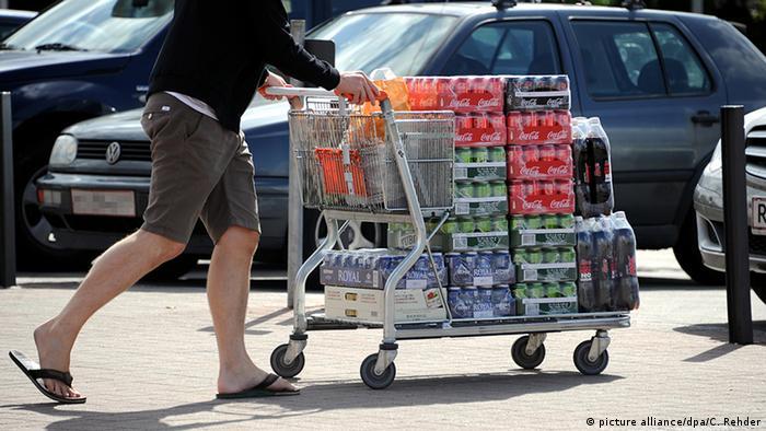 Германия, покупатель везет тележку с продуктами