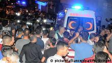 21.08.2016 epa05504453 A picture made avaliable on 21 August 2016 of people gathering on the street as ambulance cars advance to the scene after a bomb attack on a pre wedding party on 20 August evening, in a street in Gaziantep, in the southeast of Turkey, 20 August 2016. At least 50 people were killed in a suicide attack late 20 August during a henna night (a ceremony at the day before wedding) at a street in the Sahinbey district of Gaziantep city, local media reported. EPA/STRINGER Copyright: picture-alliance/dpa/EPA/Stringer