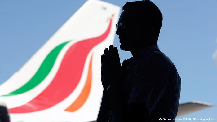 A man in silhouette prays with the tail of a Sri Lankan Airline Airbus A320 in the background