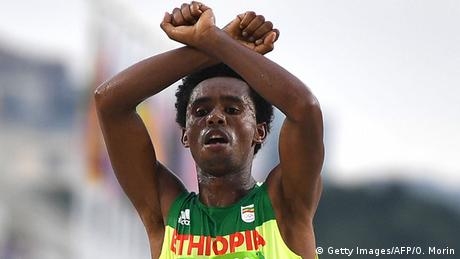 Feyisa Lilesa with arms crossed above his head.(Getty Images/AFP/O. Morin)