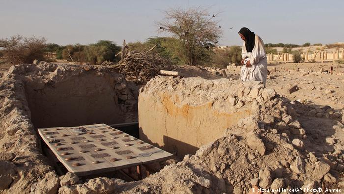 Ein Mann betet vor einem zerstörten Grab (Foto: AP)