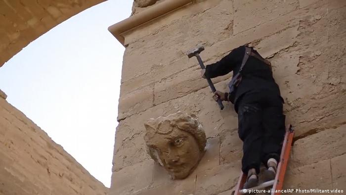 Ein IS-Kämpfer zerstört Teile des UNESCO-Welterbes in der antiken Wüstenstadt Hatra im Irak, Foto: picture-alliance/AP Photo/Militant video
