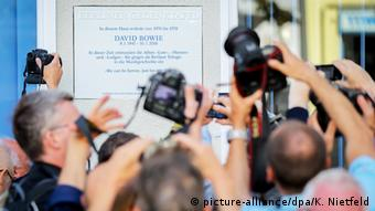 memorial plaque to David Bowie, hands holding cameras high into the air
