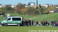 27.10.2015 ***** Flüchtlinge gehen am 27.10.2015 in Wegscheid (Bayern) hinter einem Fahrzeug der Bundespolizei. Die Asylsuchenden wurden an diesem Tag von der Polizei zu einer Notunterkunft geführt. Foto: Armin Weigel/dpa (Zu dpa Bayern will Grenzen wieder selbst kontrollieren) Copyright: picture-alliance/dpa/A. Weigel
