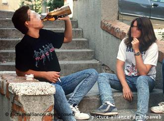 Teengers sitting on steps drinking alcohol