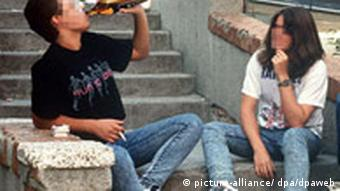 Two young men drinking beer on an outdoor staircase in Madrid