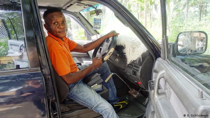 Kongo Robert Mboyo zeigt sein Auto mit dem behindertengerechten Gaspedal