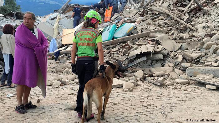 Итальянская спасательница с собакой возле разрушенного в ходе землетрясения дома