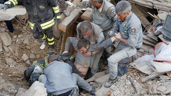 Итальянские спасатели вытаскивают из обломков дома выжившего мужчину