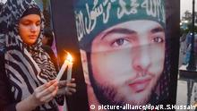 A Pakistani girl lights a candle to show solidarity with Burhan Wani