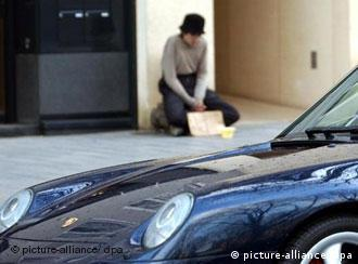 A porsche in Duesseldorf drives by a street beggar