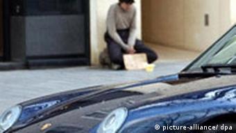 Gegensätze auf der Düsseldorfer Königsallee, aufgenommen am 16.01.2003. Ein Bettler sitzt auf dem Bürgersteig in Düsseldorf, neben ihm parkt eine Luxuslimousine (Foto: dpa)