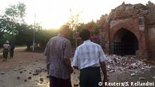 Two men look at a collapsed entrance to a pagoda after an earthquake in Bagan, Myanmar.