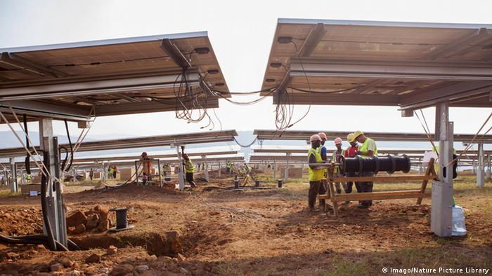 Workers gather unter two huge solar panels
