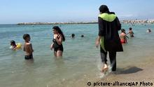 FILE - In this Aug.4 2016 file photo made from video, Nissrine Samali, 20, gets into the sea wearing traditional Islamic dress, in Marseille, southern France. The French resort of Cannes has banned full-body, head-covering swimsuits worn by some Muslim women from its beaches, citing security concerns. A City Hall official said the ordinance, in effect for August, could apply to burkini-style swimsuits. +++ (C) picture-alliance/AP Photo