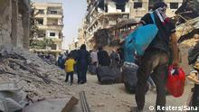 People walk among the bombed out ruins of Daraya, carrying their belongings before being evacuated.