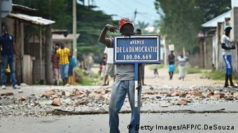 Mann hält ein Straßenschild in Bujumbura