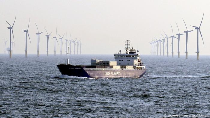Container ship crossing the ocean in front of a wind turbine farm