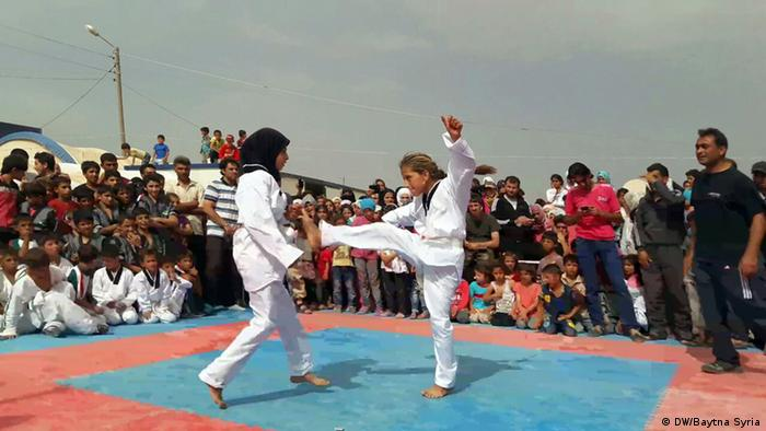 Spectators watch two kids performing martial arts