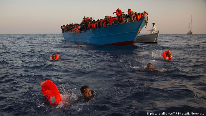 Migrants, most of them from Eritrea, jump into the water from a crowded wooden boat