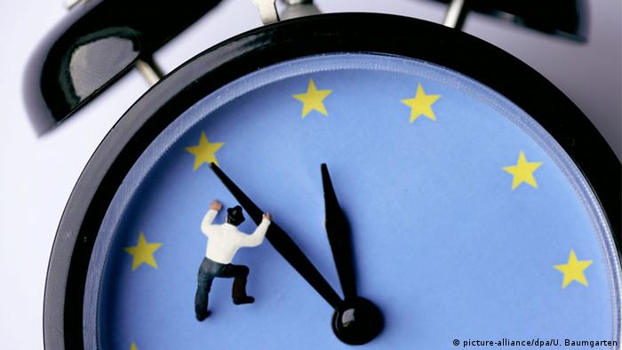 Clock at five between 12 with the EU flag on the face and a figure of a man hanging from the second hand ((c) picture-alliance/dpa/U. Baumgarten)