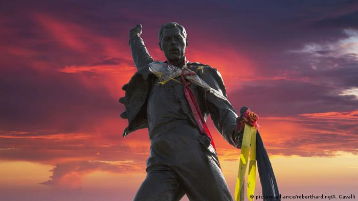 A statue in Switerzland of Freddy Mercury in front of a dramatic sunset (Foto: dpa)