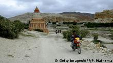 17.06.2016 *** This picture taken on June 17, 2016 shows a Nepalese man riding his motor bike in Lo Manthang in Upper Mustang. A biannual trade fair in Tibet offers a rare opportunity for those living in the remote former Buddhist kingdom of Upper Mustang in Nepal to cross the usually closed border into China, which is cultivating closer ties with the Himalayan nation. / AFP / PRAKASH MATHEMA / TO GO WITH AFP STORY: Nepal-China-Tibet-Religion-Border FEATURE by Ammu Kannampilly (Photo credit should read PRAKASH MATHEMA/AFP/Getty Images) © Getty Images/AFP/P. Mathema