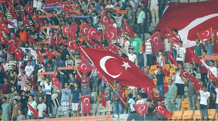 Fans wave Turkish flags during football game.