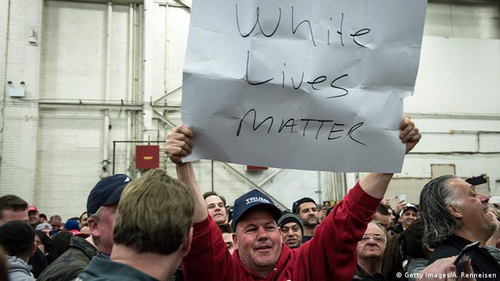 A Trump supporter holds up a 'White Lives Matter' sign during a rally for Republican Presidential Candidate Donald Trump