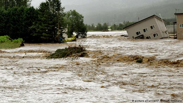 Floodwaters from the Sorachi river wash away a building in Japan after Typhoon Lionrock hit in August 2016 (picture-alliance/AP Photo/R. Ominato)