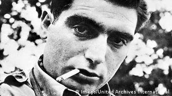 Retrato do fotógrafo Robert Capa com um cigarro na boca