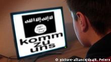 Symbolbild zu den Anwerbeversuchen der radikal-islamistischen IS Islamischer Staat bei minderjährigen Jugendlichen Jugendlicher sitzt am Bildschirm eines PC s mit Flagge des IS komm zu uns | Verwendung weltweit (c) picture-alliance/dpa/R. Peters