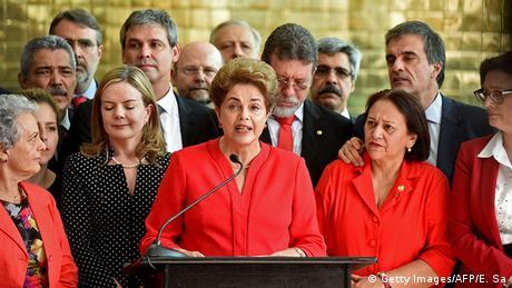 Dilma, de vermelho, rodeada por apoiadores, fala ao microfone.