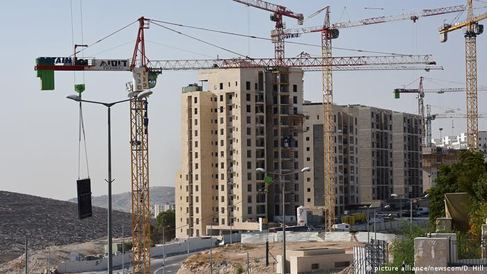 Building cranes stand near new housing units under construction in the Israeli settlement of Har Homa in southern east Jerusalem (picture alliance/newscom/D. Hill)