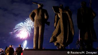 Spectators watch as fireworks explode in the sky in front of the Victory Monument