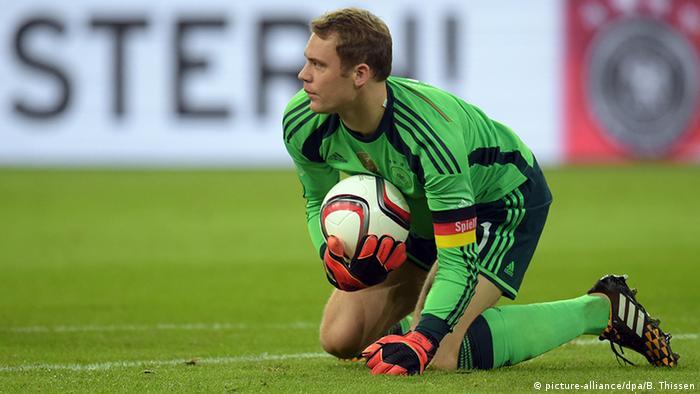 Goleiro da seleção alemã, Manuel Neuer, faz uma defesa. Ele está usando a braçadeira de capitão.