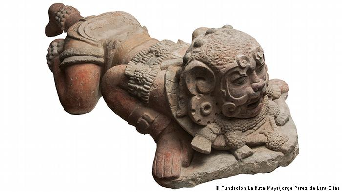 Eine Kalksteinskulptur zeigt einen Mann mit Maske des Jaguargottes, der als Mischung aus Mensch und Tier geformt ist.