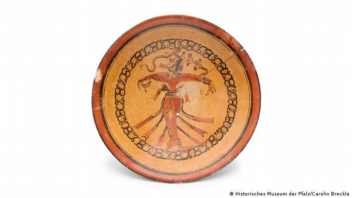 Ein Maya-Teller mit einer Gott-Abbildung, die am Unterkörper mehrere Paddel besitzt.